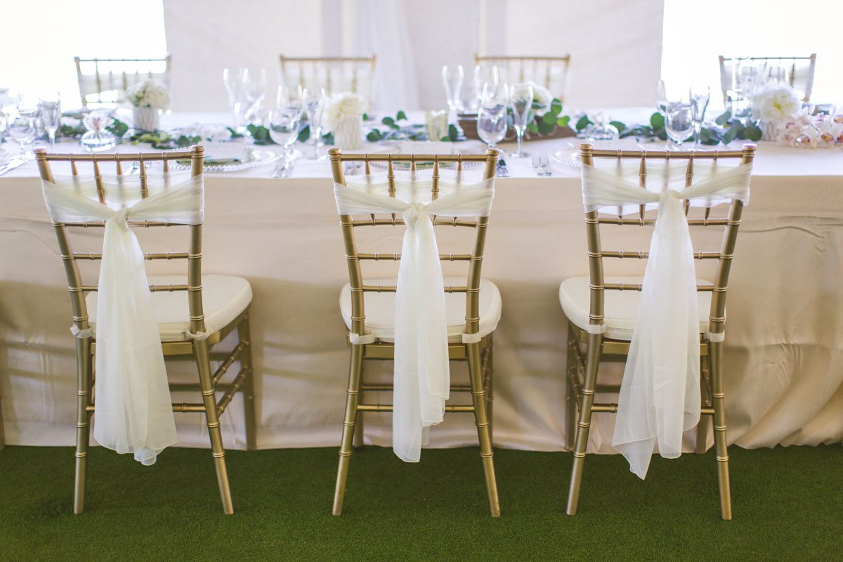 _Chairs with white linens tied TAWed0460