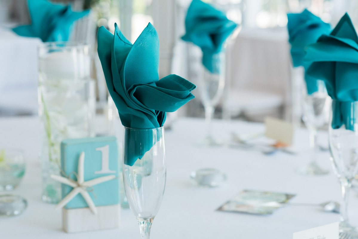 Close up of teal linens inside champaign flutes Pearl_Warnock_Caroline__Evan_Photography_MichaelaChrisWedding1697