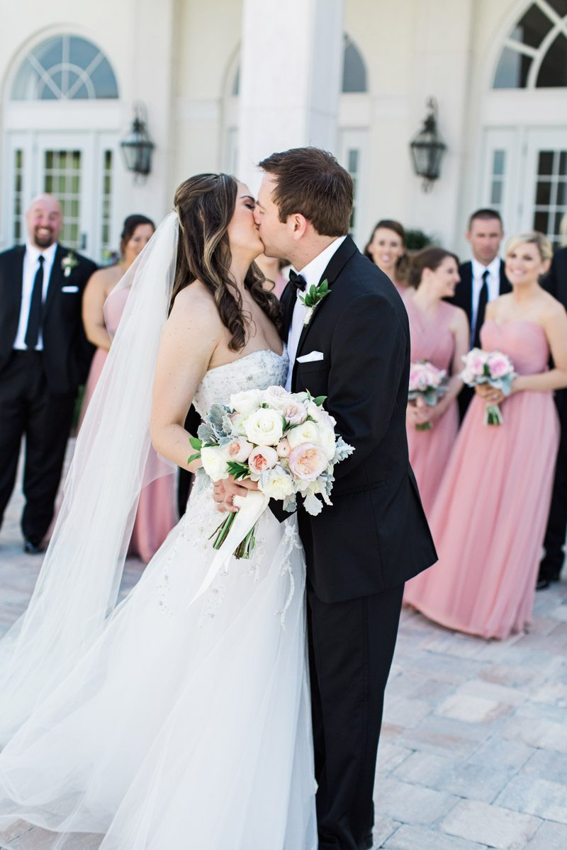 Groom and bride kissing with bridal party in background christyandtaylor-w-0365