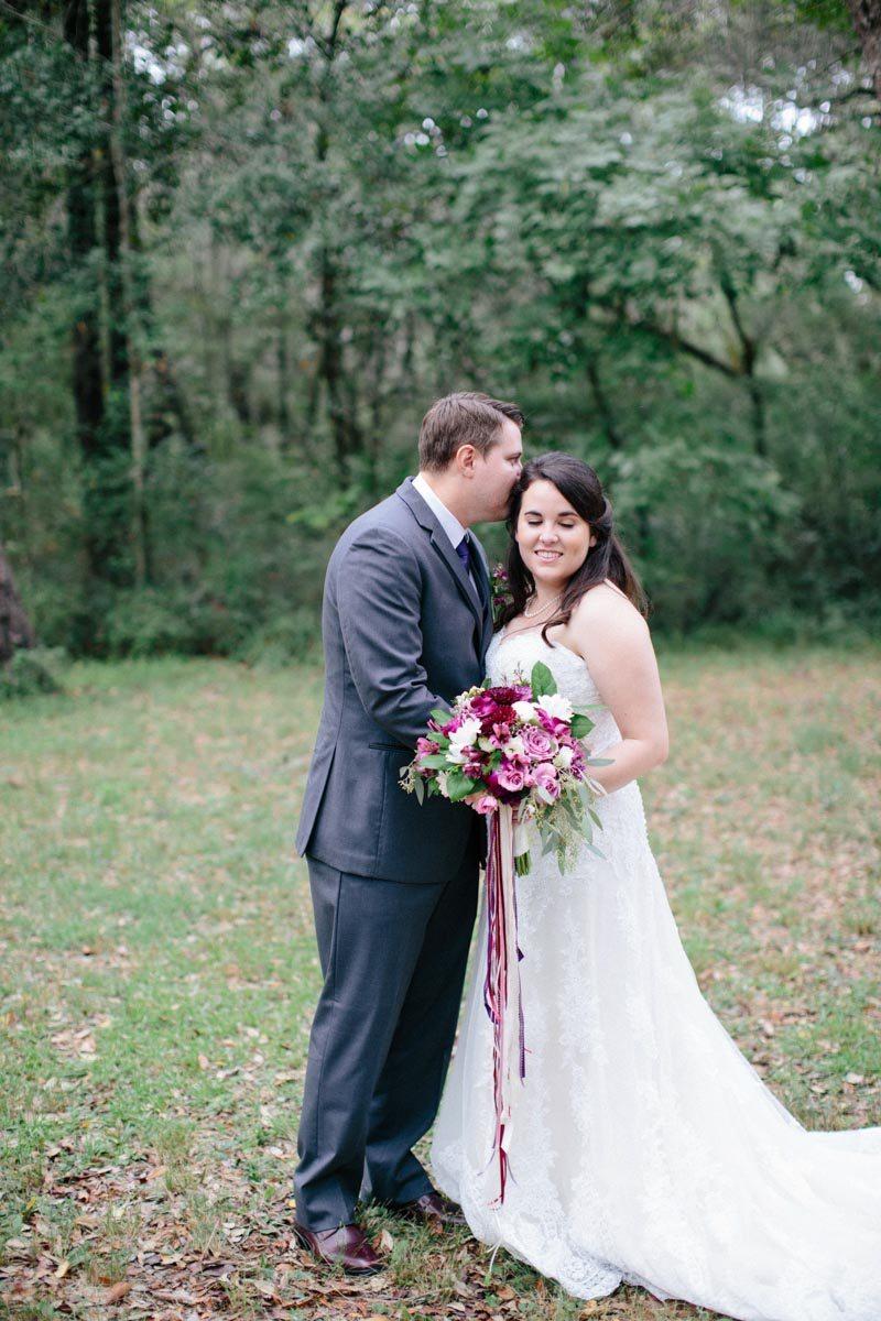_Groom kissing bride's head while holding bouquet Obert_Taylor_Ais_Portraits_AisPortraitsBryanTori110