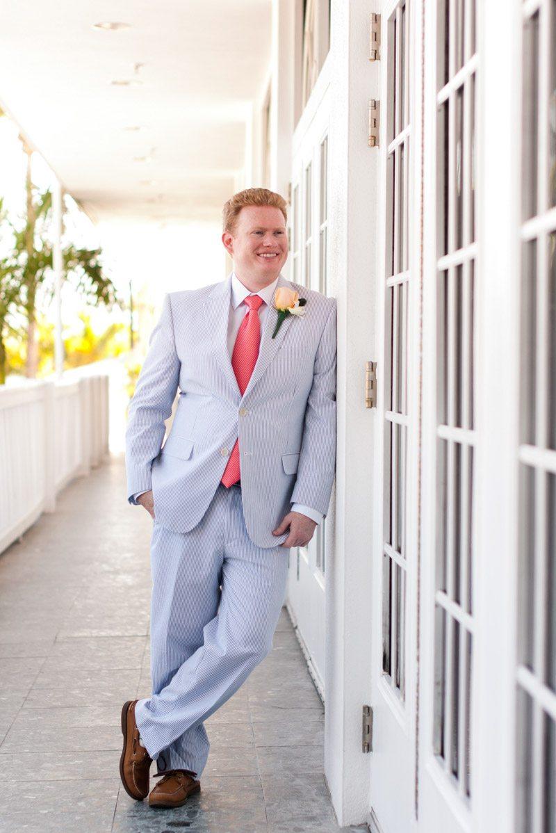 Groom lounging against door in light grey tux and coral tie Pearl_Warnock_Caroline__Evan_Photography_MichaelaChrisWedding0633