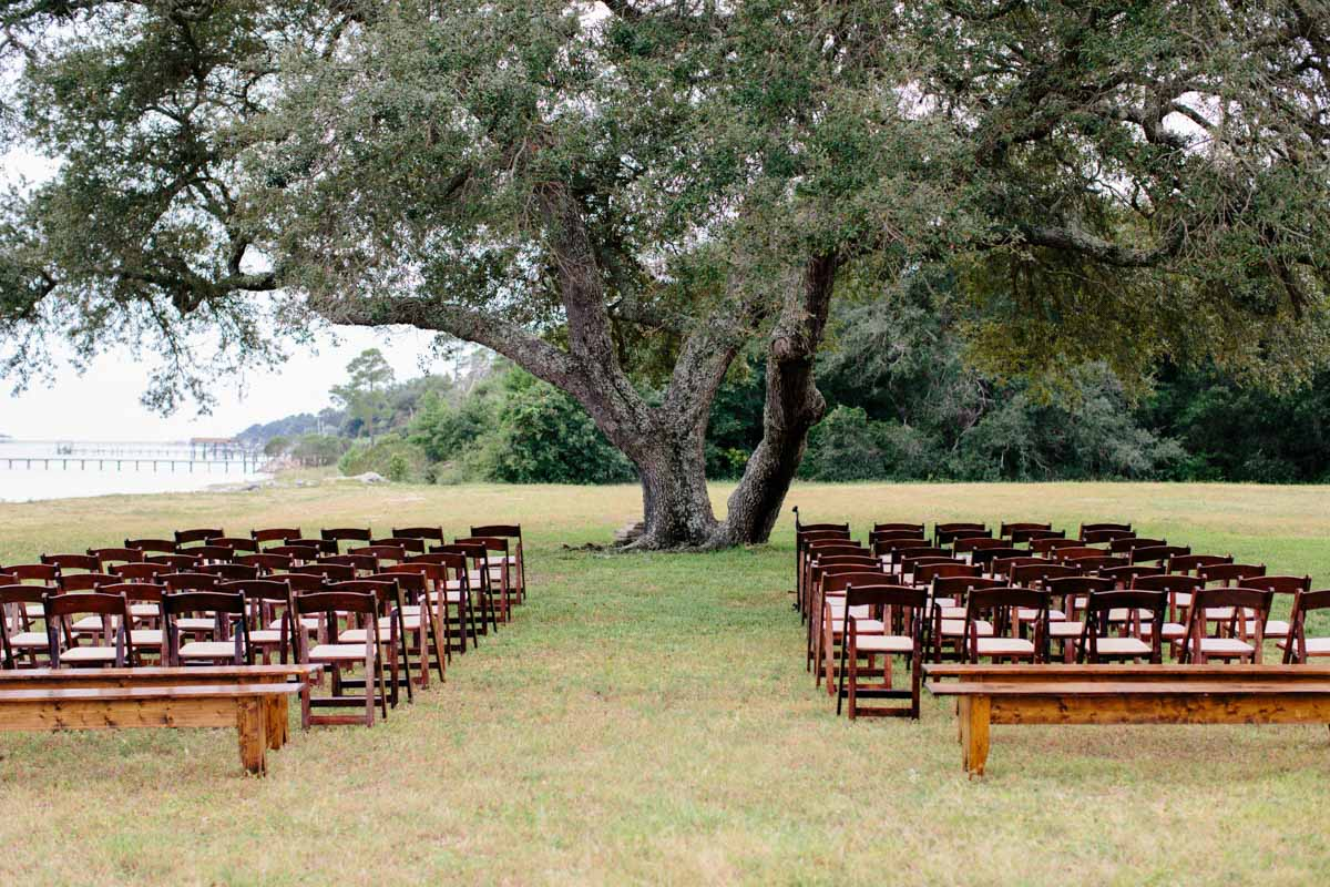 _Outdoor ceremony with brown chairs and benches in front of tree Obert_Taylor_Ais_Portraits_AisPortraitsBryanTori201