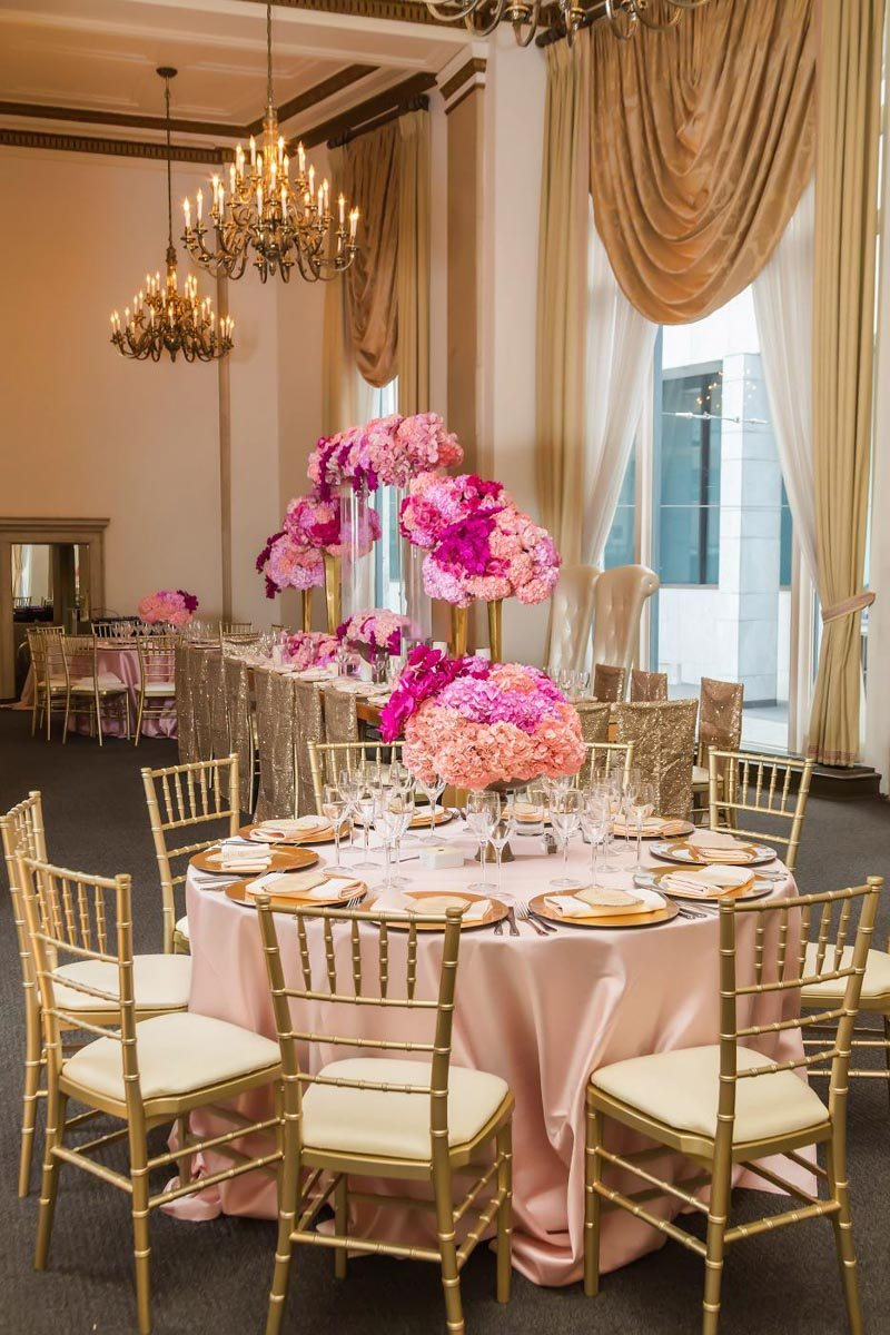 Reception with chandeliers gold and bronze pink flowers