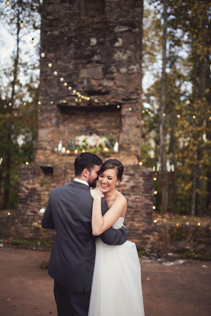 bride and groom laughing vintage brick