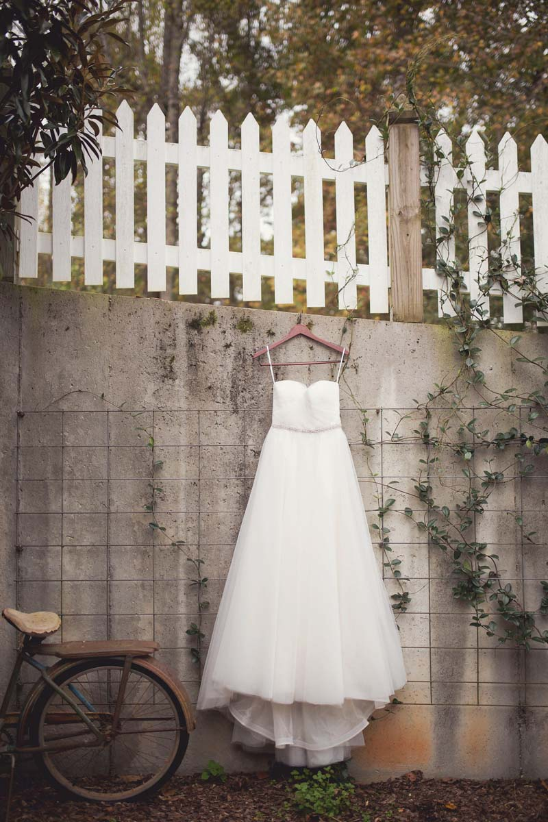 dress hanging on old wall white picket fence and rusty bike