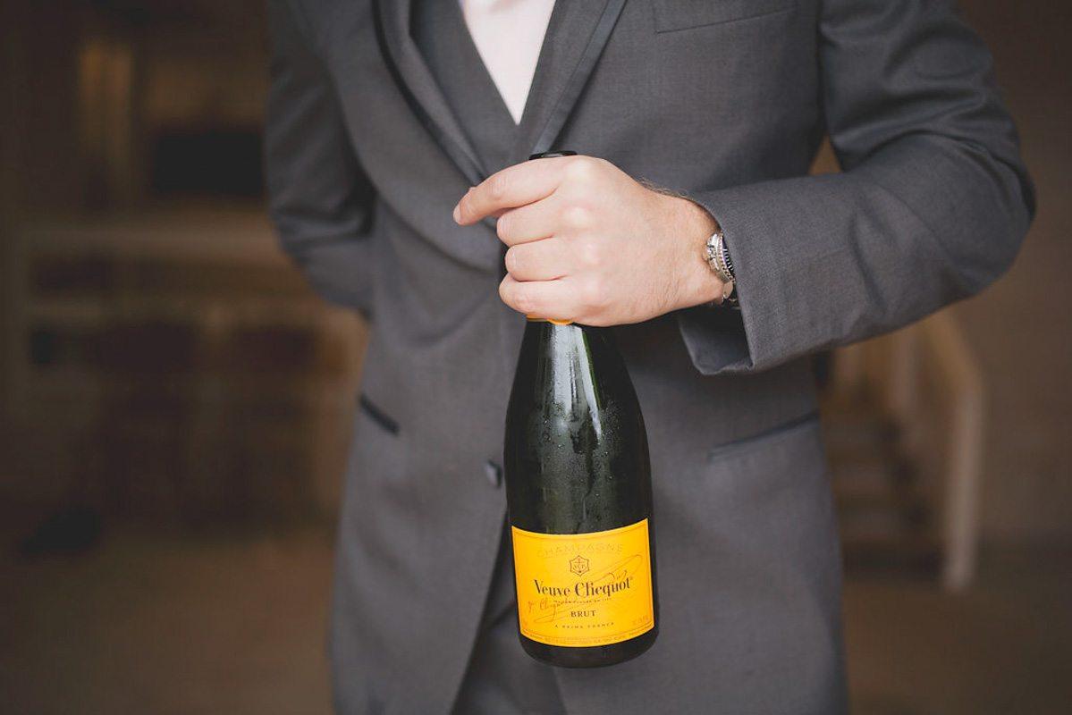 gray suit Veuve Clicquot champagne