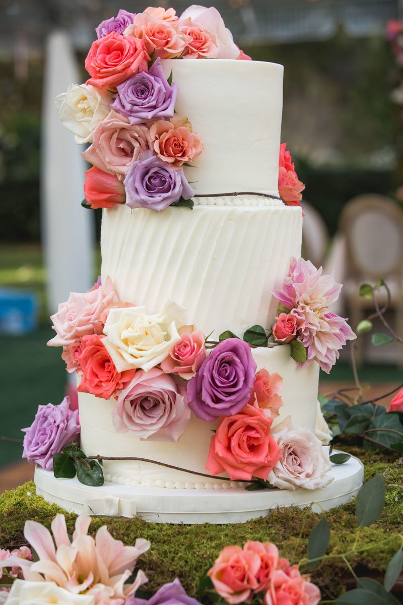 triple tiered cake with pink and purple flowers