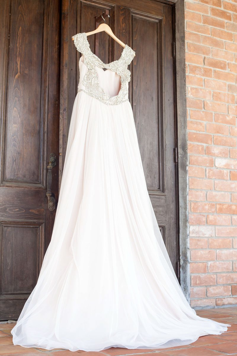 Beaded wedding dress hanging from wooden door Smith_Neesley_Sarah_Melyssa_Photography_IMG0024