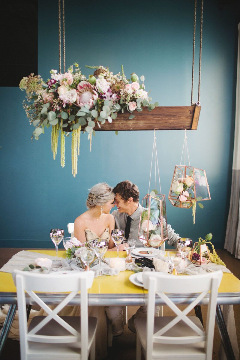 Bride and groom sitting at boho floral table