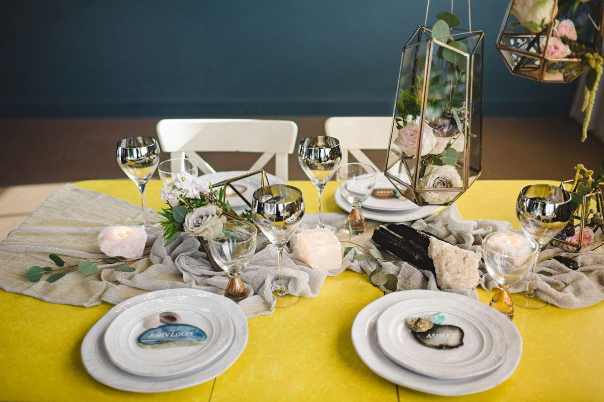 Colored geode stones and greenery on table