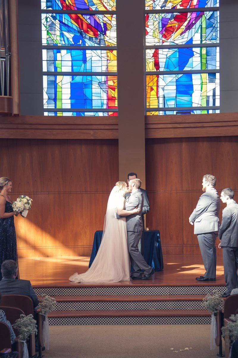 First kiss after ceremony with stain glass background Smith_Neesley_Sarah_Melyssa_Photography_IMG00882