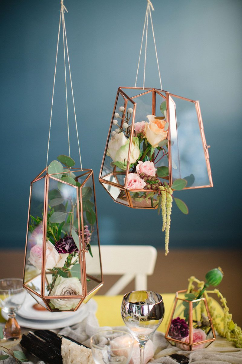 Gold hanging geometric cases with flowers inside