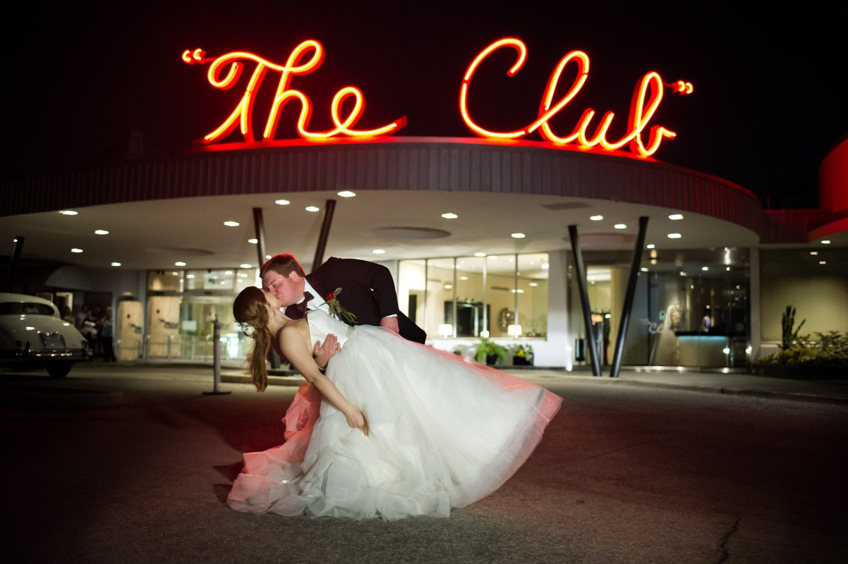 Groom dipping and kissing bride outside The Club