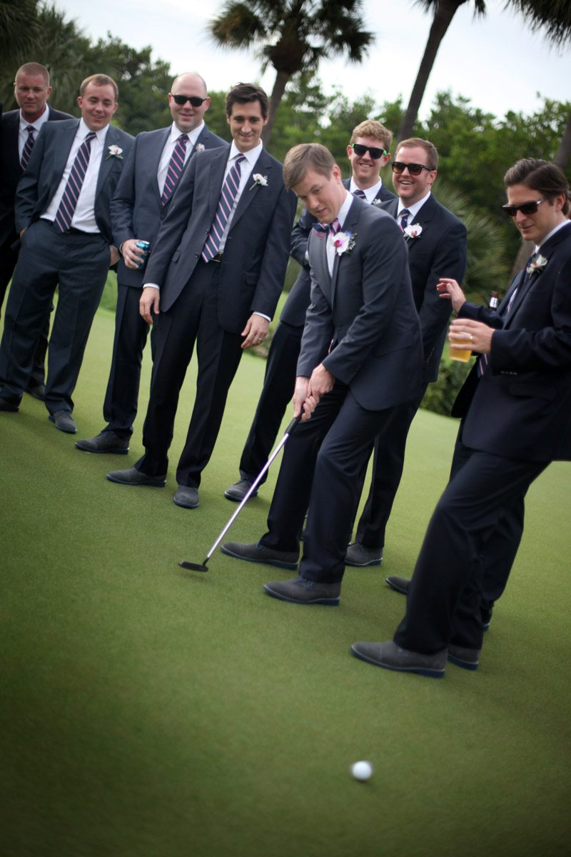 Groomsmen with groom playing golf