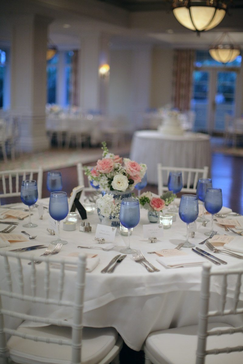 Reception white table and chairs blue glasses