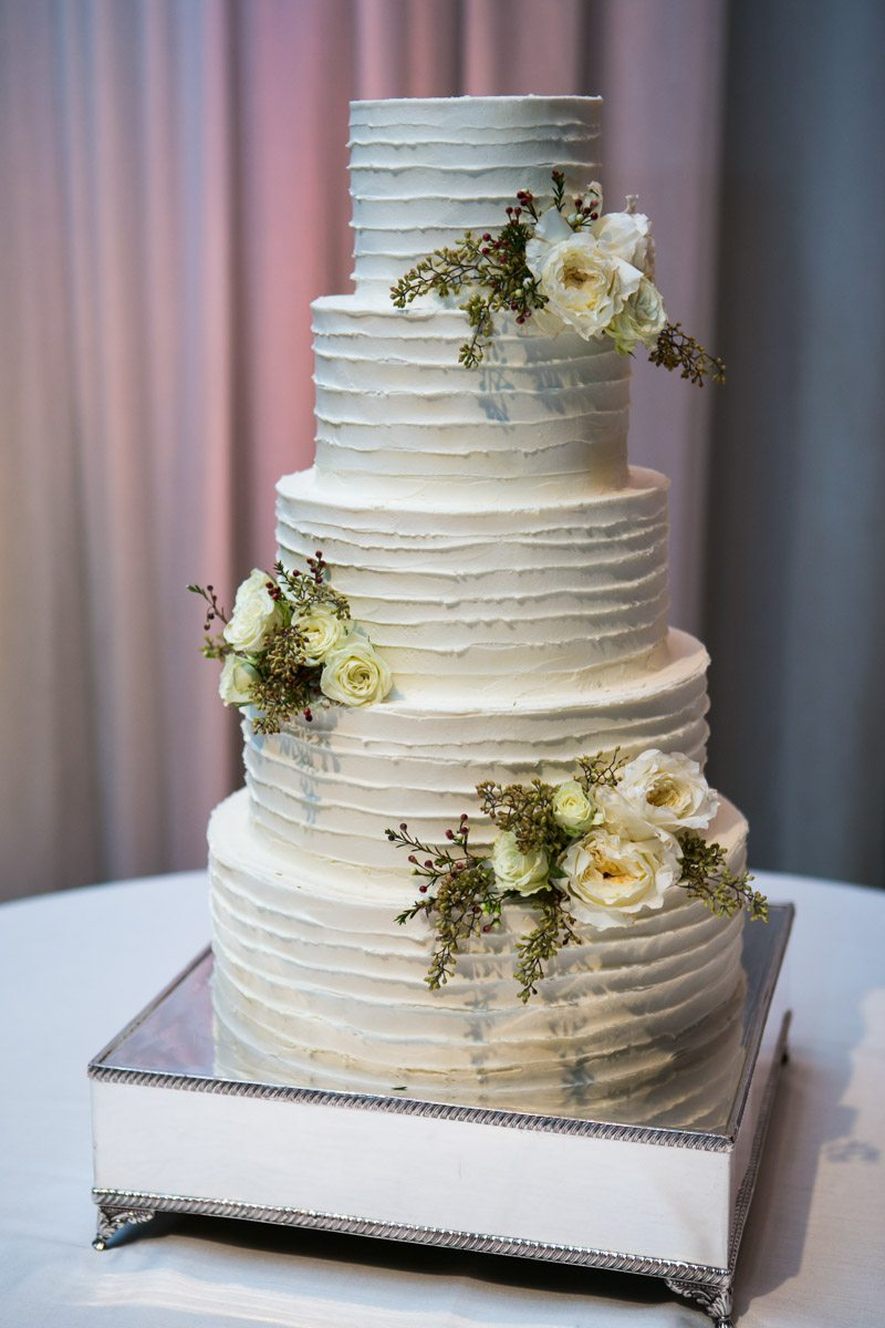 Tiered white wedding cake with white flowers