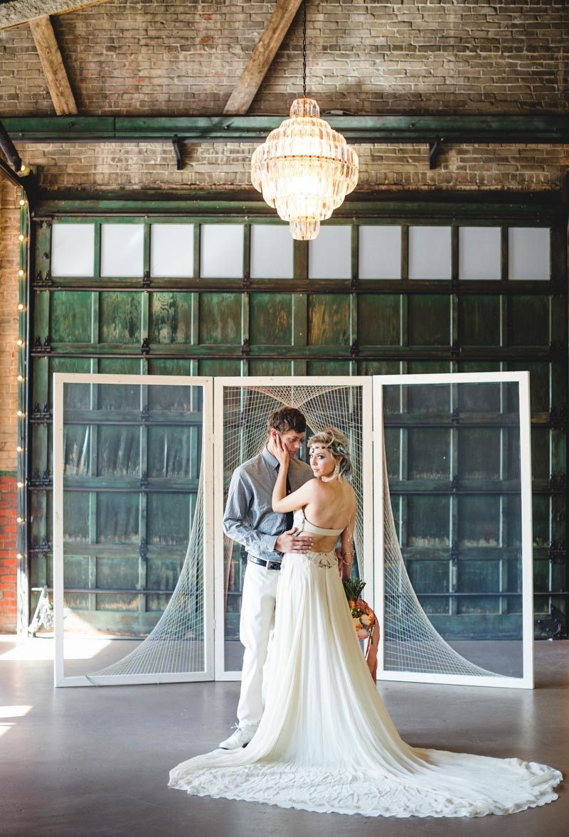 Wedding dress fanned out bride and groom posing under chandelier in front of netting