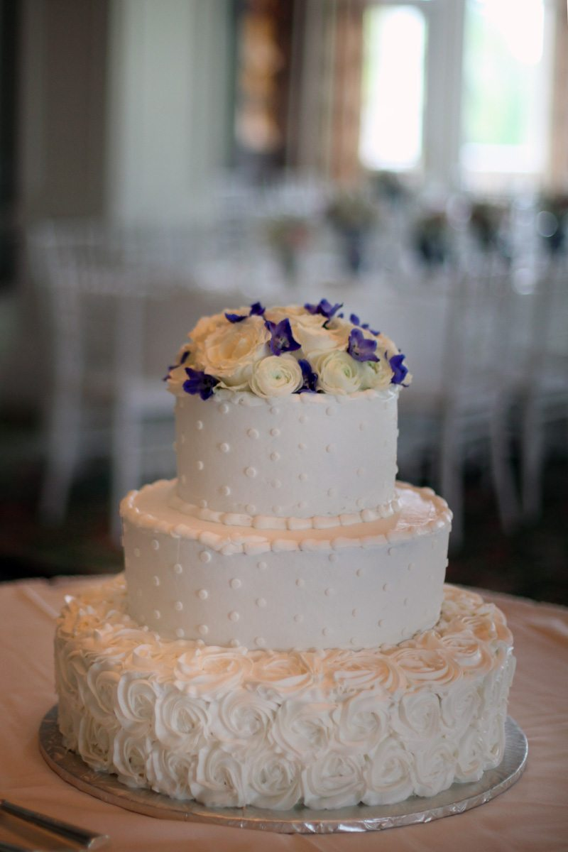 White three tiered wedding cake blue flowers on top