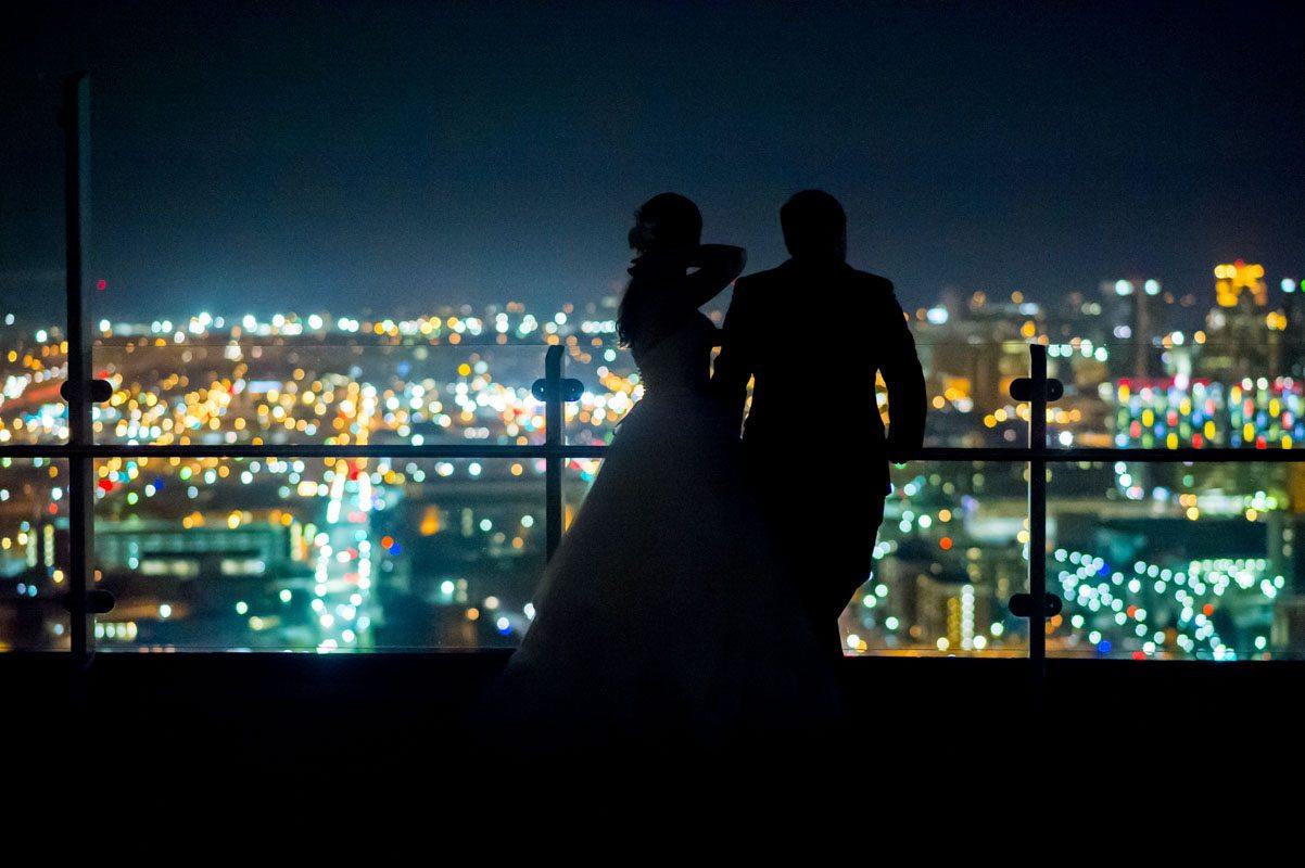 bride and groom overlooking city skyline