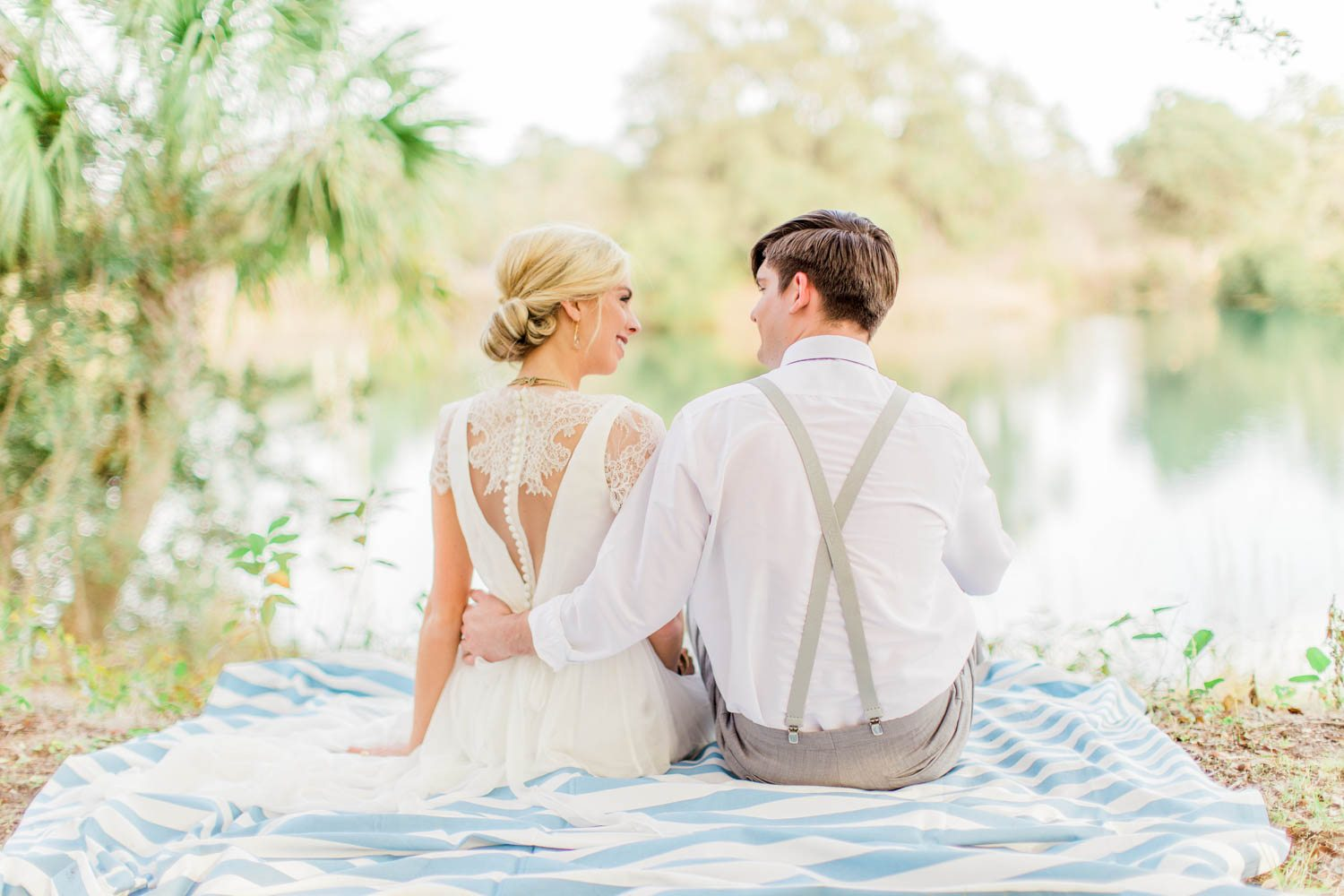 back of bride and groom sitting outdoor wedding