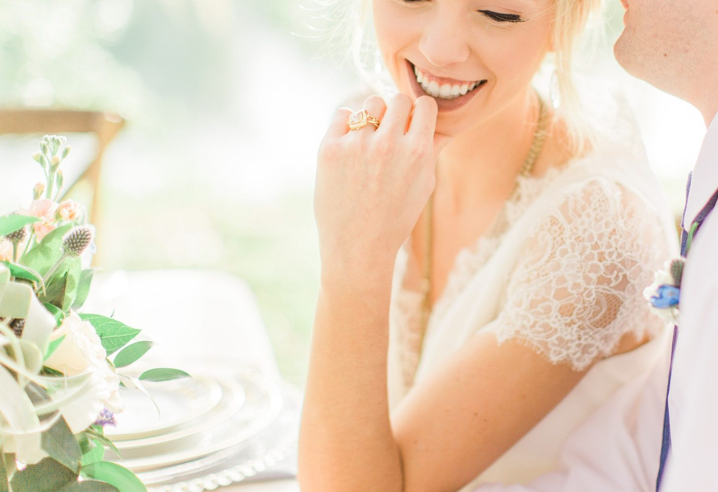close up of gold wedding ring and lace wedding dress