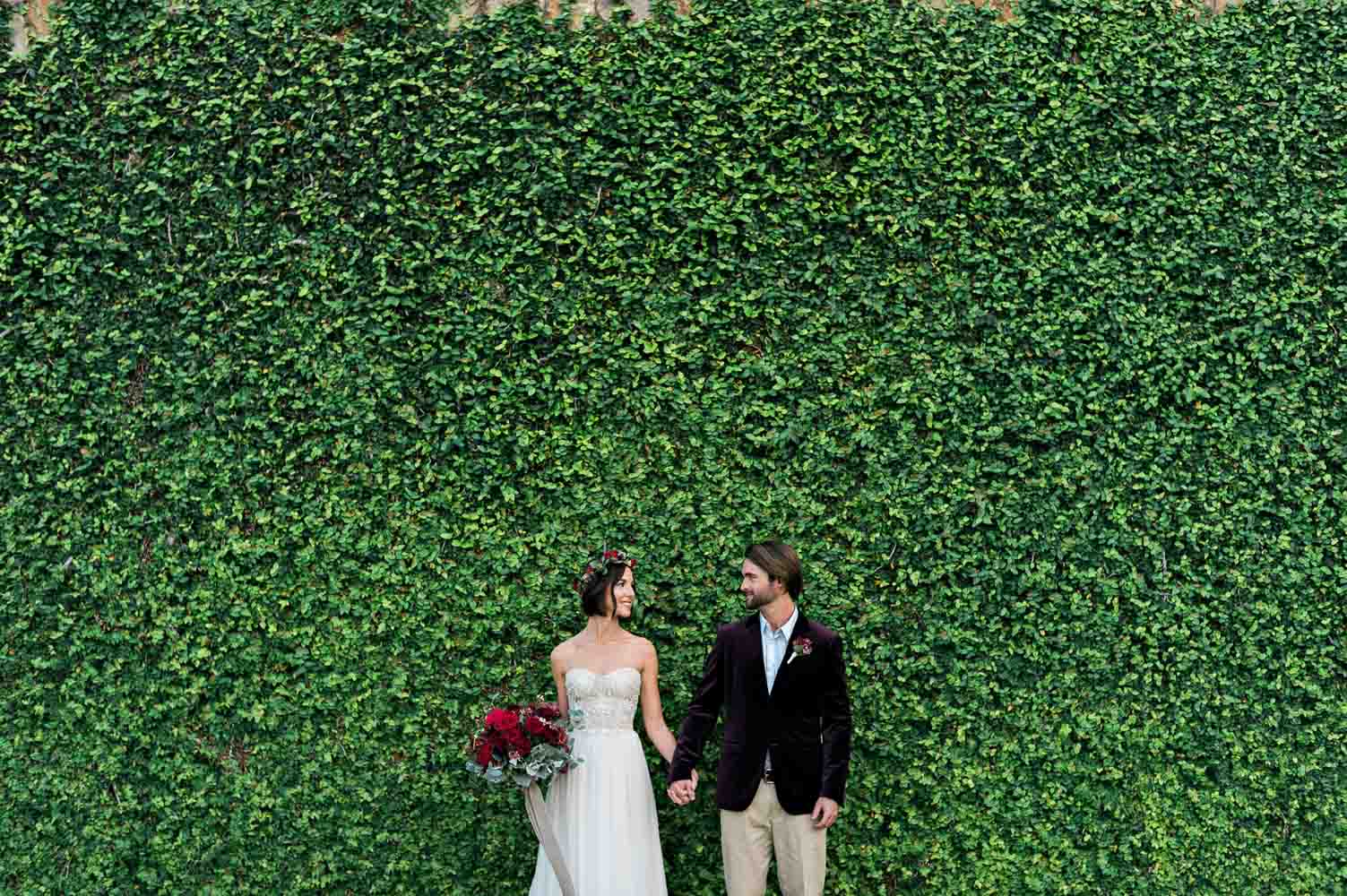bride and groom in front of green hedge wall maroon italian wedding inspiration