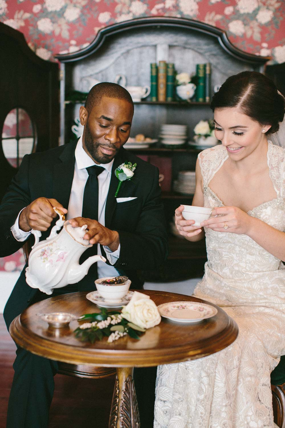 bride and groom having tea in detailed floral china