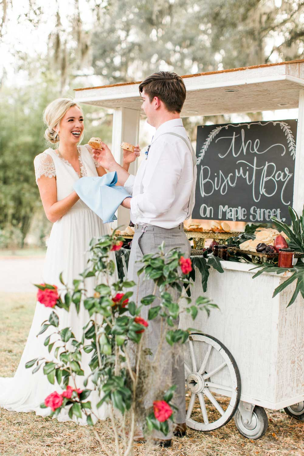 bride and groom eating from biscuit bar southern outdoor wedding