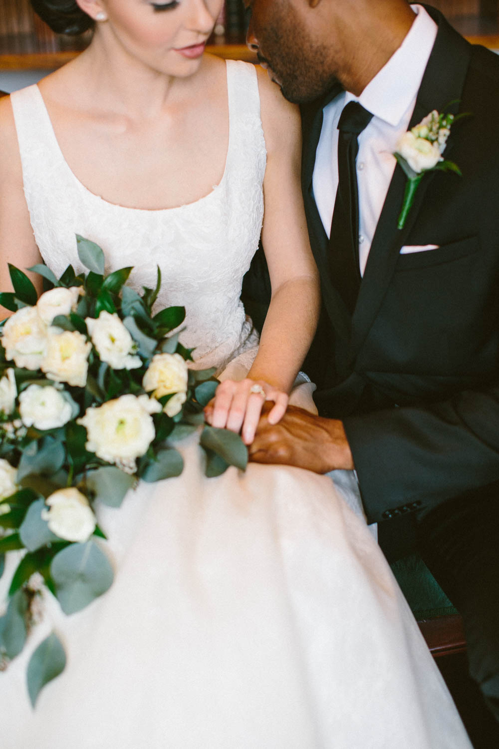 close up of bride and groom in black and white holding hands and white rose bouquet