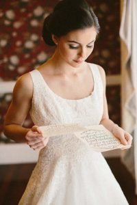 bride in beaded detail dress looking at cream stationery with caligraphy