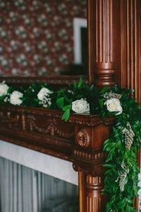 white rose garland hanging off wooden fireplace mantel