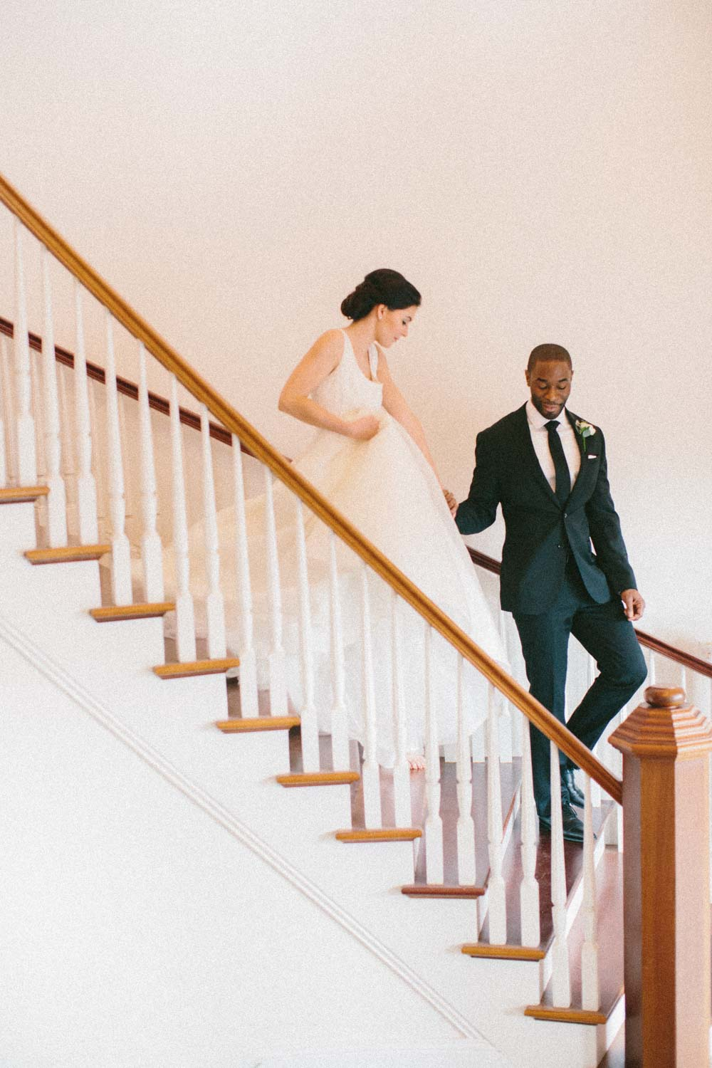 groom helping bride down stair while she holds her dress