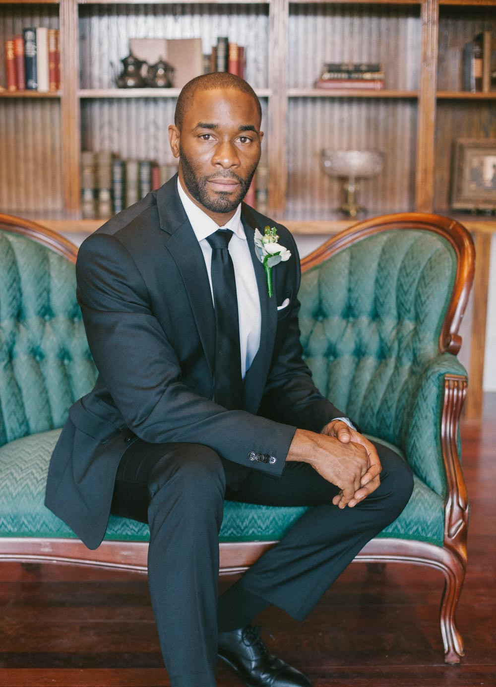 groom portrait on emerald chair