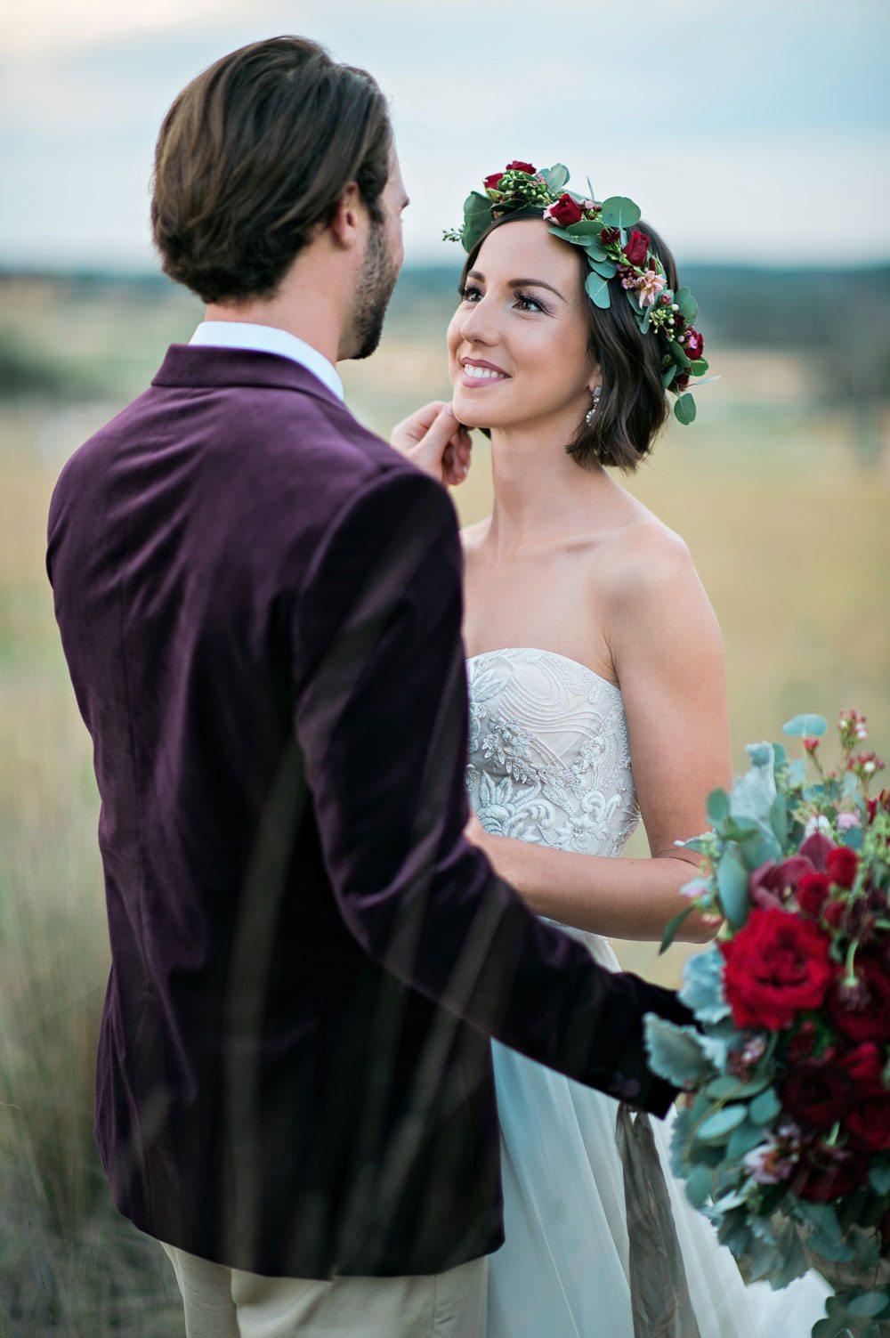 bride with flower crown and groom with maroon velvet jacket