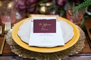 gold maroon and yellow table place setting