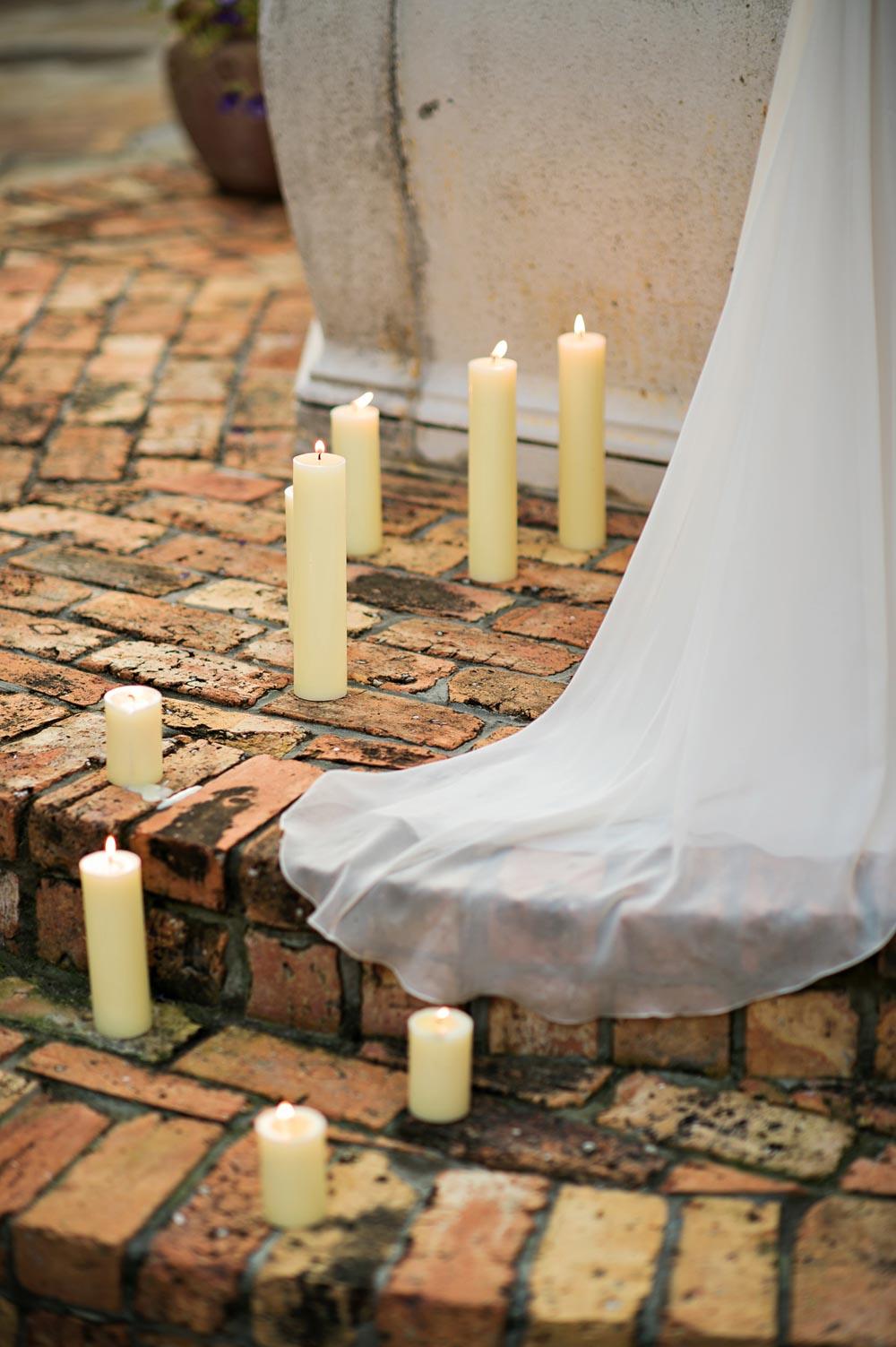 white candles on brick wedding altar