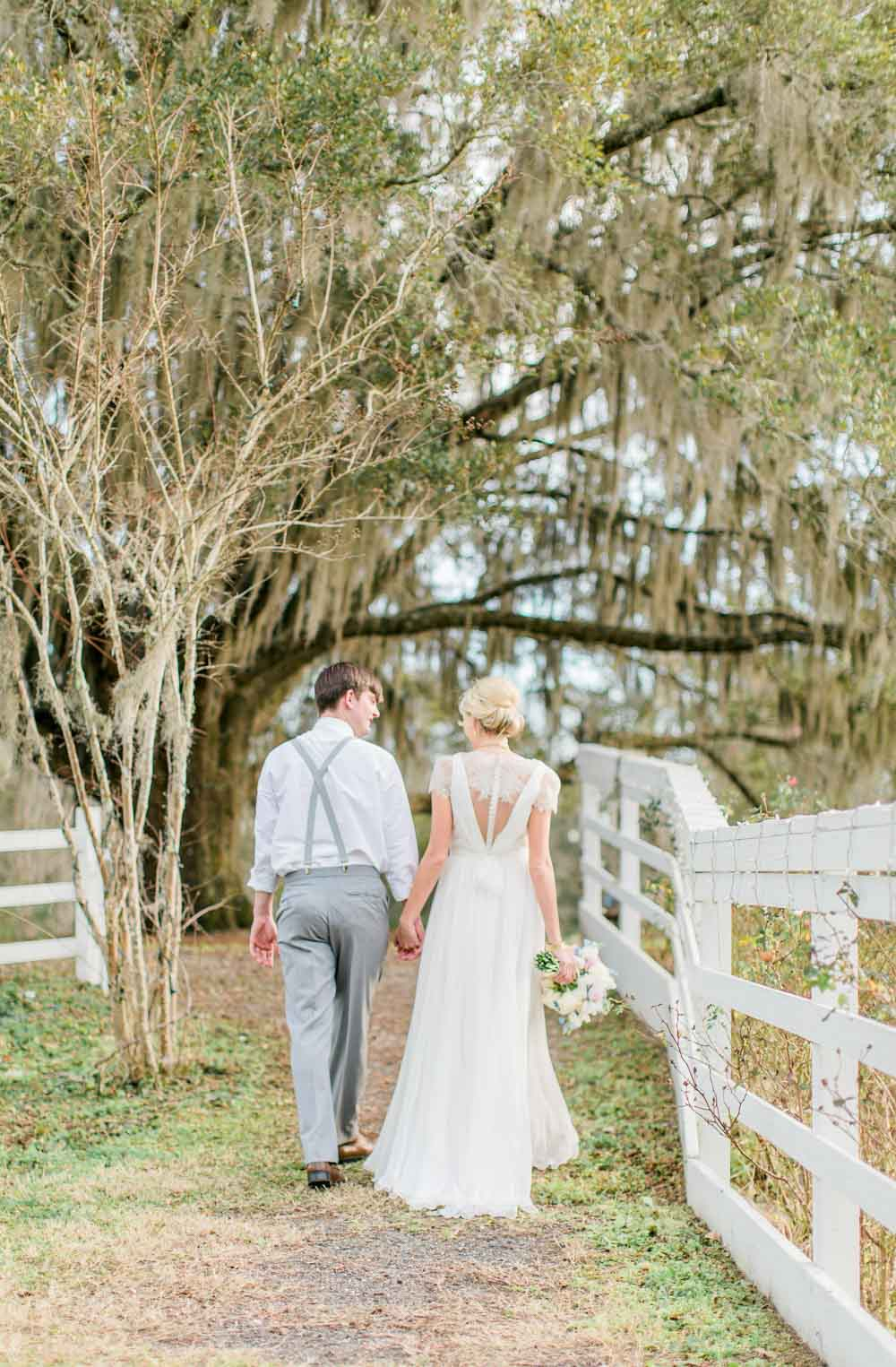 bride and groom walking down path in lace wedding dress holding bouquet