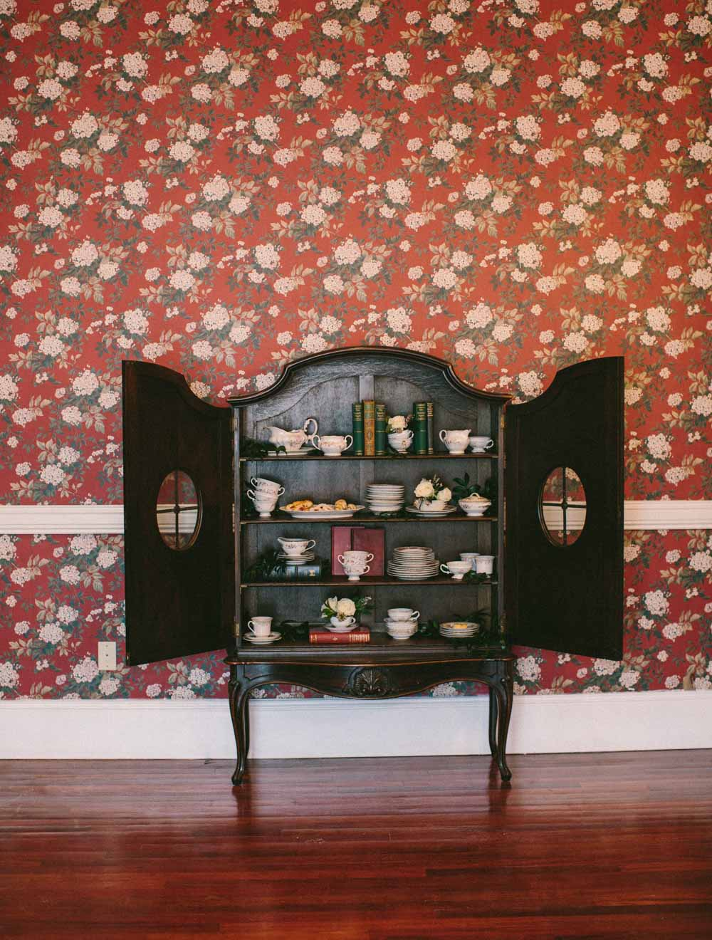 open cabinet doors with china books and roses
