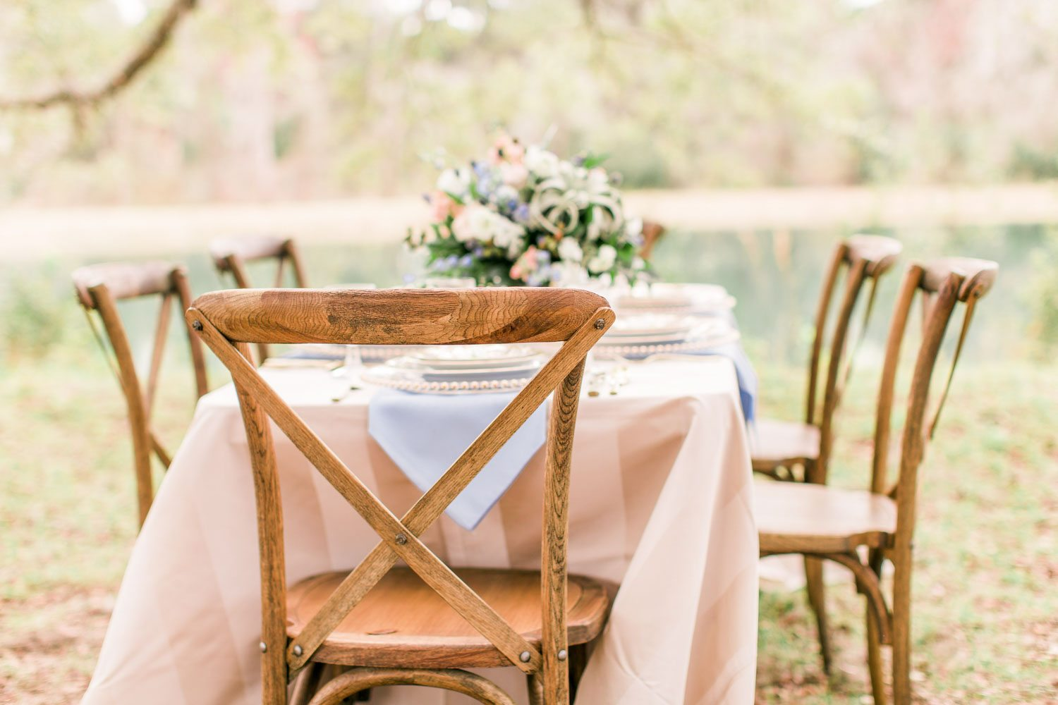 peach table clothed table with flowers and wooden chairs