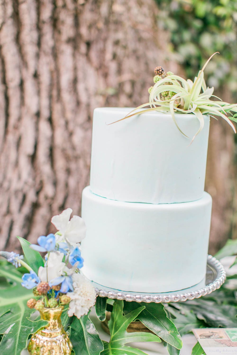simple pastel blue wedding cake with floral details