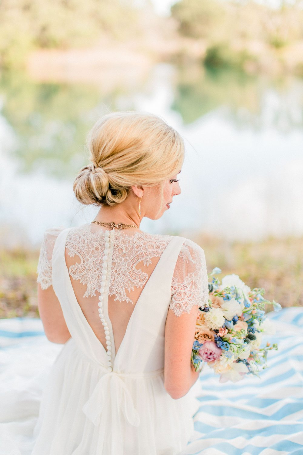 lace wedding dress back detail with updo hair holding bouquet