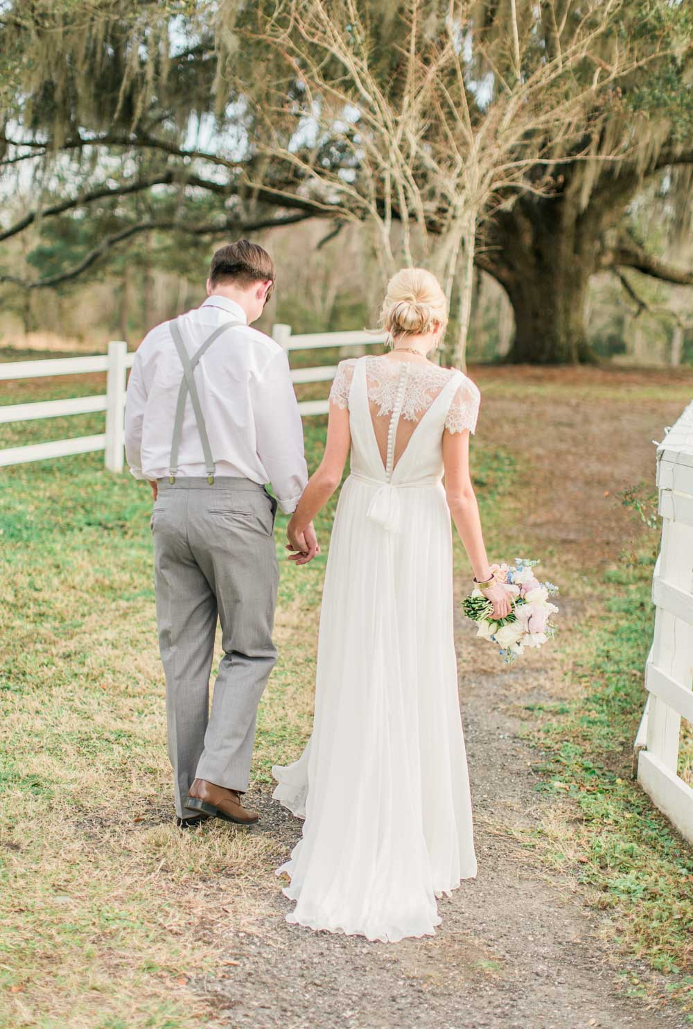 bride and groom walking down path holding hands outdoor wedding
