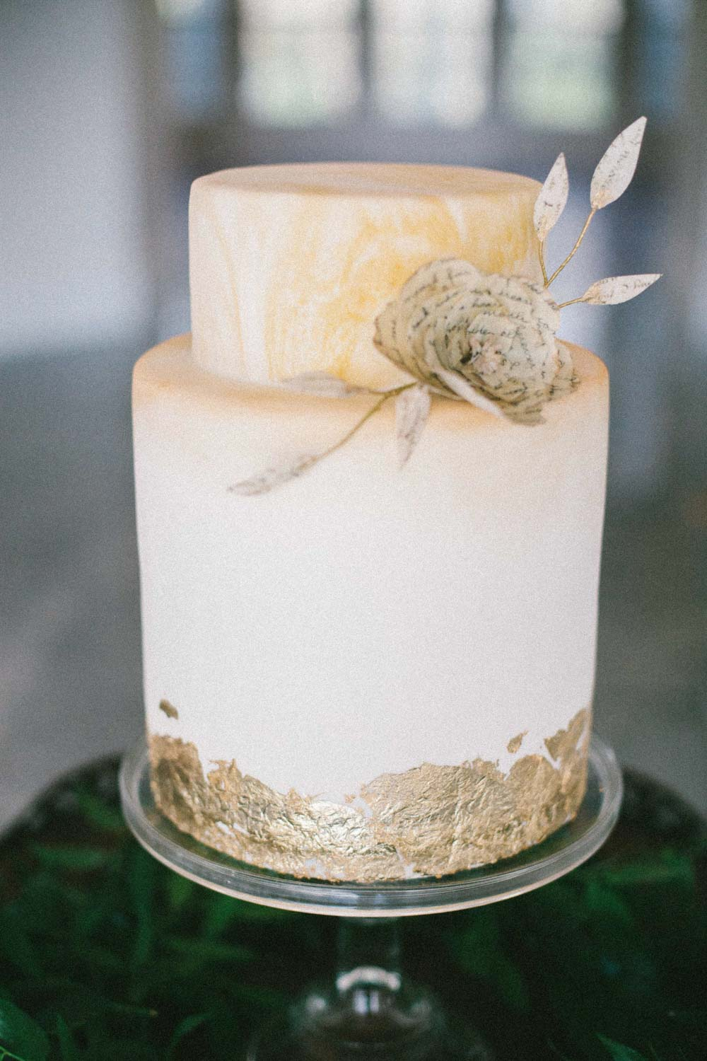white and gold leaf wedding cake with flower