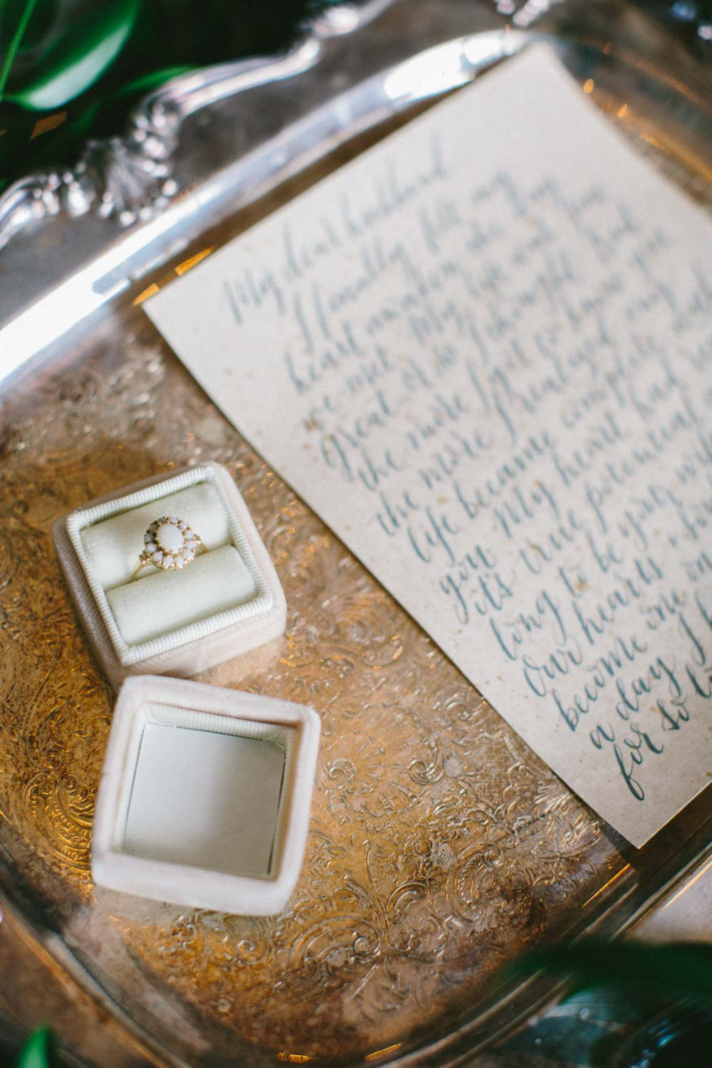 white and gold ring with letter on silver platter