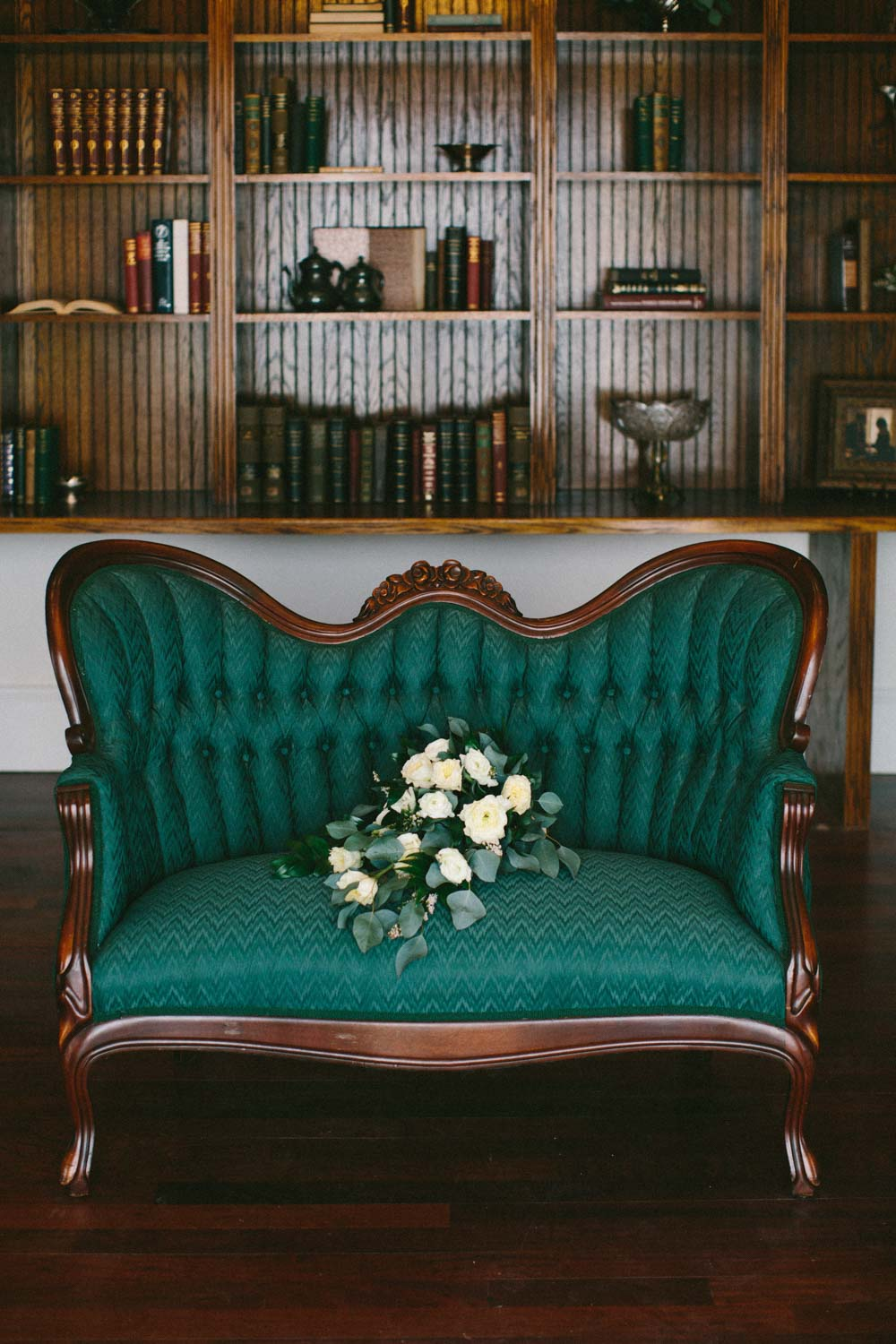 white rose bouquet on emerald couch