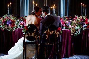 colorful bold wedding table purple gold red pink maroon bride and groom signs centerpieces flowers candles