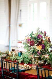 gold blue green red magenta floral arrangement candles wedding table