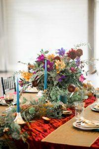 colorful wedding table decor purple magenta red orange floral arrangements gold glassware plates blue candles