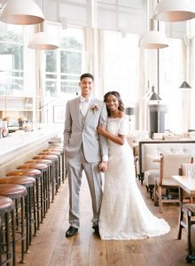bride groom gray tuxedo lace off the shoulder wedding dress pink boutonniere