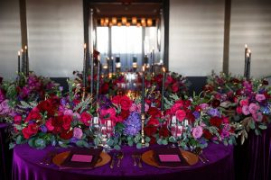 colorful reception tables purple pink red gold maroon candles flowers